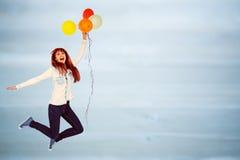 Imagem composta da mulher de sorriso do moderno que guarda balões Fotos de Stock
