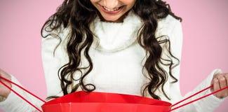 Imagem composta da mulher feliz com o chapéu do Natal que olha no saco de compras vermelho imagem de stock