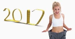 Imagem composta da mulher fina que veste calças velhas após peso perdedor Fotografia de Stock Royalty Free