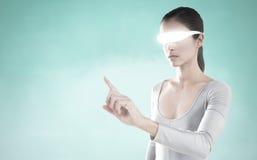 Imagem composta da mulher que aponta ao usar vidros video virtuais Fotografia de Stock