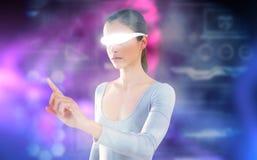 Imagem composta da mulher que aponta ao usar vidros video virtuais Imagens de Stock