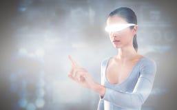 Imagem composta da mulher que aponta ao usar vidros video virtuais Foto de Stock