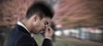 Imagem composta da opinião lateral o homem de negócios com a cabeça à disposição que sofre da dor de cabeça fotos de stock