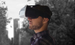 Imagem composta da opinião lateral o homem novo que veste vidros da realidade virtual Fotografia de Stock Royalty Free