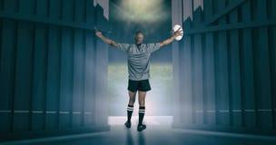 A imagem composta da opinião traseira o atleta com braços levantou guardar a bola de rugby 3d Fotografia de Stock Royalty Free