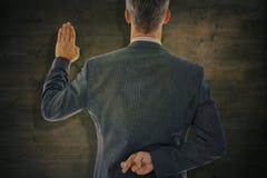Imagem composta da opinião traseira o homem de negócios que toma o juramento com os dedos cruzados fotos de stock royalty free