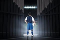 Imagem composta da opinião traseira o jogador de futebol que guarda o futebol 3d Foto de Stock