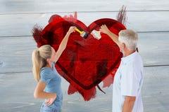Imagem composta da parede feliz da pintura dos pares com pincéis Imagens de Stock Royalty Free