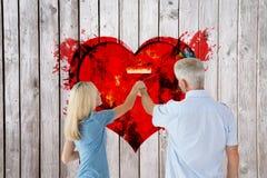 Imagem composta da parede feliz da pintura dos pares com rolo Fotos de Stock Royalty Free