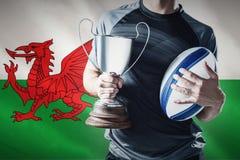 Imagem composta da seção mestra do jogador bem sucedido do rugby que guarda o troféu e a bola Imagens de Stock Royalty Free