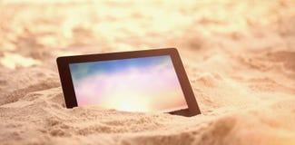 A imagem composta da tabuleta digital manteve-se na areia na praia Fotos de Stock