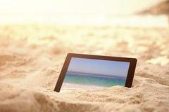 A imagem composta da tabuleta digital manteve-se na areia na praia Fotografia de Stock Royalty Free