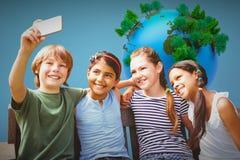 Imagem composta das crianças felizes que tomam o selfie no parque foto de stock royalty free