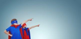 Imagem composta das crianças mascaradas que fingem ser super-herói imagens de stock royalty free
