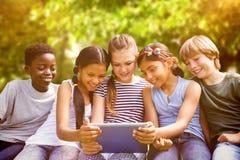 Imagem composta das crianças que usam a tabuleta digital no parque imagens de stock