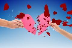Imagem composta das mãos que guardam duas metades de coração quebrado Foto de Stock