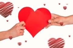 Imagem composta das mãos que guardam o coração vermelho Foto de Stock Royalty Free