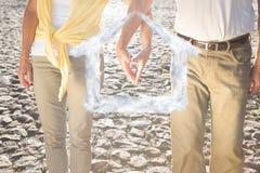 Imagem composta das mãos tocantes dos pares superiores felizes Foto de Stock