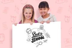 Imagem composta das meninas atrás de um painel vazio Imagens de Stock