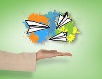 Imagem composta de aviões de papel fêmeas de apresentação da mão Imagem de Stock