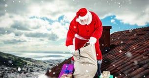 Imagem composta de caixas de presente de enchimento de Papai Noel no saco Imagens de Stock
