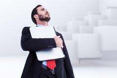 Imagem composta de concentrar o homem de negócios no terno que guarda o portátil foto de stock