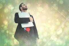 Imagem composta de concentrar o homem de negócios no terno que guarda o portátil fotos de stock royalty free