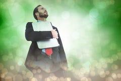 Imagem composta de concentrar o homem de negócios no terno que guarda o portátil imagens de stock