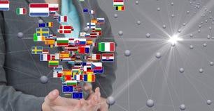 Imagem composta de Digitas da mulher de negócios que está com bandeiras e os pontos de conexão Fotos de Stock Royalty Free