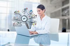 Imagem composta de Digitas da mulher de negócios que usa o portátil por ícones de SEO no escritório Fotos de Stock Royalty Free