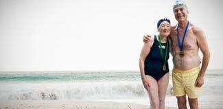 Imagem composta de medalhas vestindo dos pares superiores felizes imagens de stock