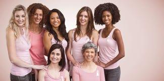 Imagem composta de mulheres de sorriso nos equipamentos cor-de-rosa que levantam para a conscientização do câncer da mama imagens de stock