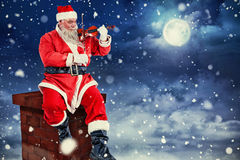 Imagem composta de Papai Noel de sorriso que joga o violino na cadeira Imagens de Stock