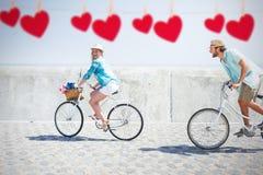 A imagem composta de pares bonitos em uma bicicleta monta Imagem de Stock