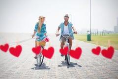 A imagem composta de pares bonitos em uma bicicleta monta Foto de Stock Royalty Free