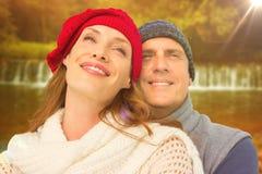 Imagem composta de pares felizes na roupa morna Foto de Stock Royalty Free