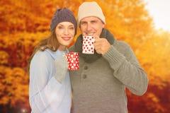 Imagem composta de pares felizes na roupa morna que guarda canecas Foto de Stock