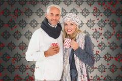 A imagem composta de pares felizes no inverno forma guardar canecas Foto de Stock