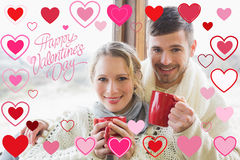 Imagem composta de pares loving na roupa do inverno com os copos de café contra a janela Fotografia de Stock