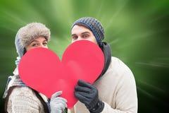 Imagem composta de pares novos atrativos na roupa morna que guarda o coração vermelho Fotografia de Stock
