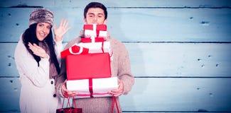 Imagem composta de pares novos com muitos presentes de Natal imagem de stock