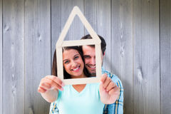 A imagem composta de pares novos felizes com casa dá forma imagem de stock royalty free