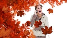 Imagem composta de rir a morena bonito em telefonar da forma do inverno imagem de stock royalty free