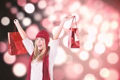 Imagem composta de sacos de compras levando louros bonitos Imagens de Stock Royalty Free