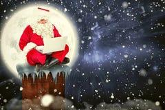 Imagem composta de Santa que senta e que usa seu portátil Imagem de Stock Royalty Free