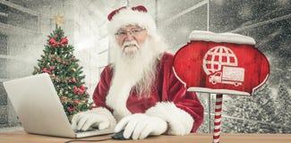 A imagem composta de Santa surfa no Internet Imagens de Stock Royalty Free