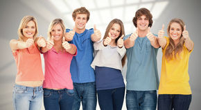 Imagem composta de seis amigos que dão os polegares acima como sorriem Foto de Stock Royalty Free