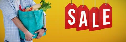 Imagem composta de vegetais levando do homem no saco de compras contra o fundo branco fotos de stock