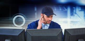 Imagem composta do agente da segurança que escuta o fone de ouvido ao usar o computador na mesa imagens de stock royalty free