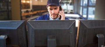 Imagem composta do agente da segurança que fala no telefone ao usar o computador na mesa foto de stock